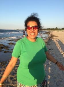 Lydia am Strand mit ausgebreiteten Armen, grünes T.Shirt und buntem Rock